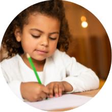 Imagen de Nena con guardapolvo escribiendo sobre papel