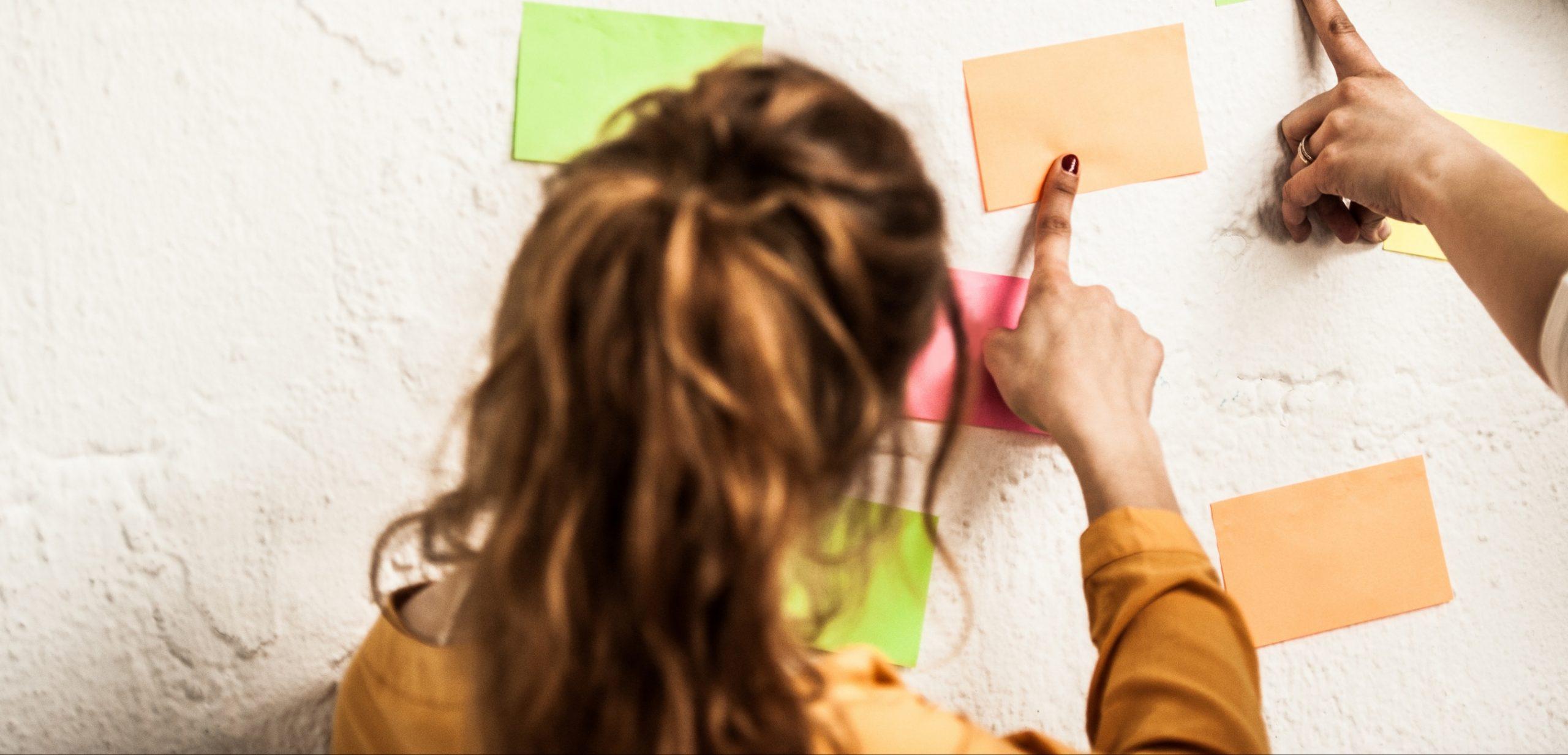 """Imagen de portada de """"El Equipo"""" en donde se visualiza una chica escribiendo en un postit"""