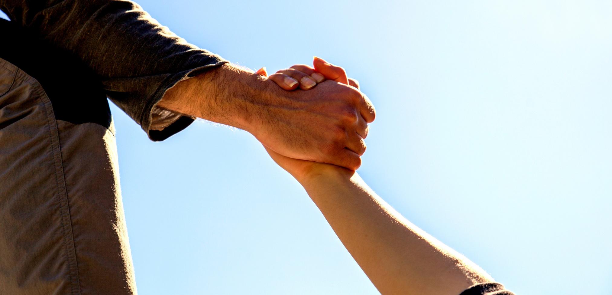 """Imagen de portada de sección """"Impacto social"""" en donde se visualiza una mano agarrando y levantando la de otra persona"""