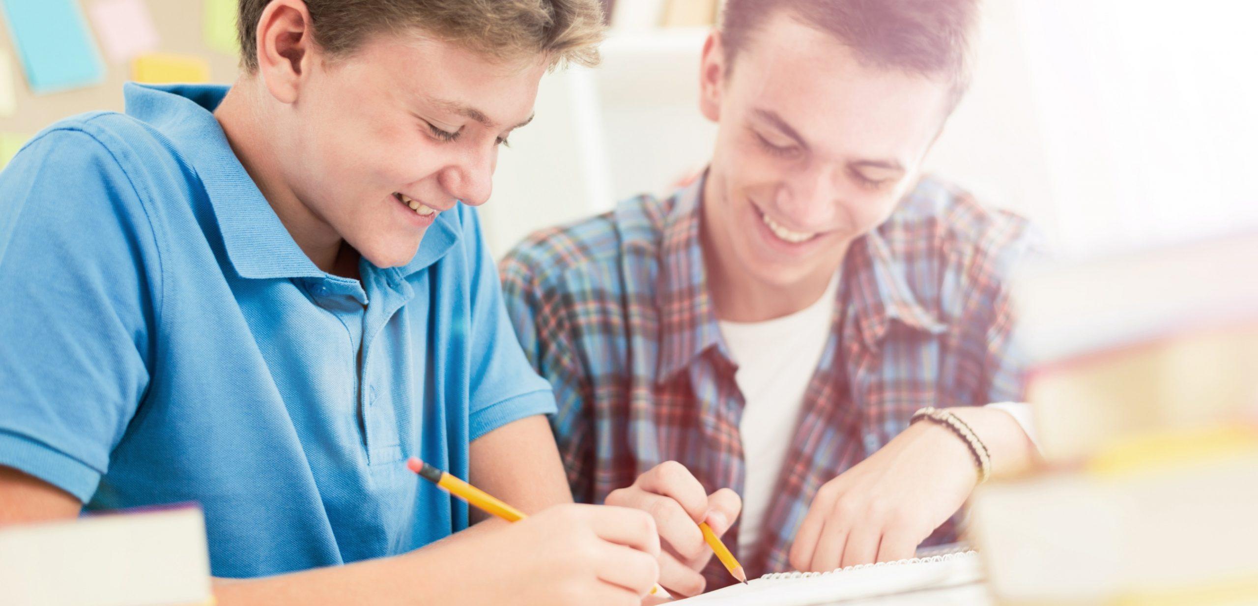 """Imagen de portada de sección """"Modelo educativo"""" en donde se ve a dos chicos sonriendo mientras estudian"""